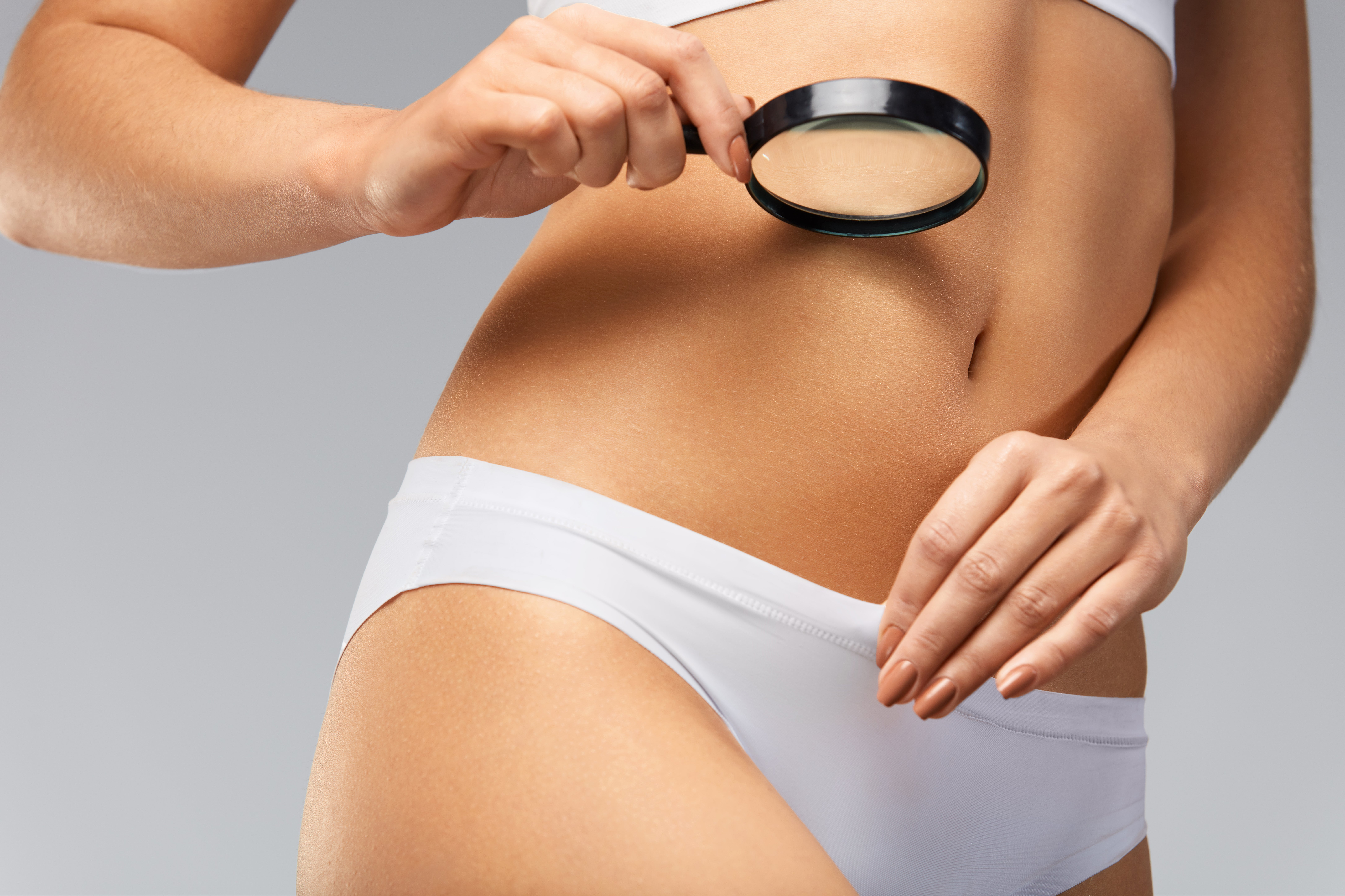a woman holds a magnifying glass up to her body