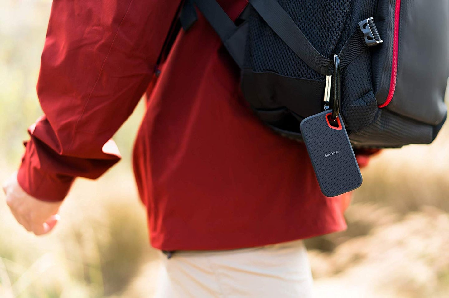 person walking with a backpack and ssd drive attached