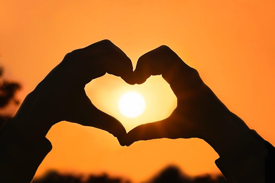 hands making a heart around the sun