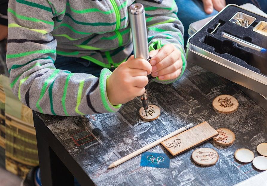 kid burning design into wood