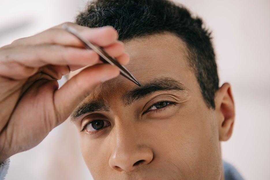 man tweezing eyebrow