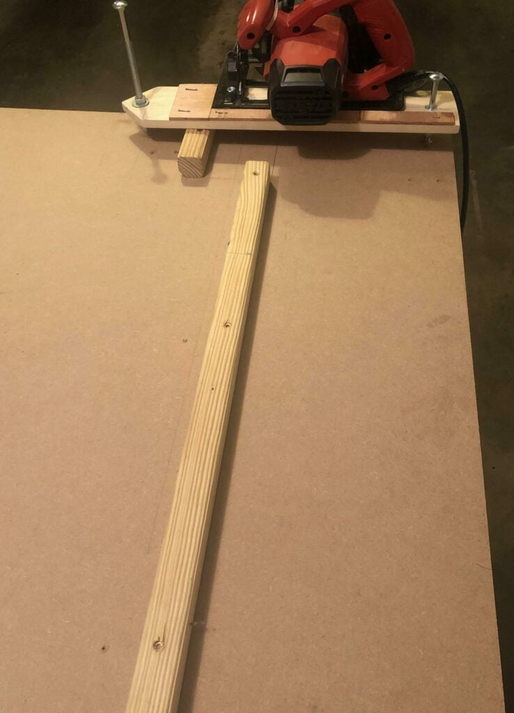a work surface with a chop saw jig and a wood-cutting guide fence