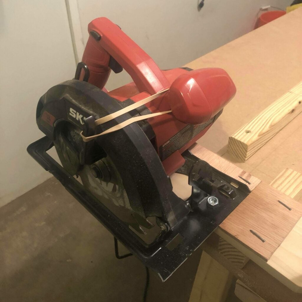 a circular saw with the blade guard locked open with a rubber band