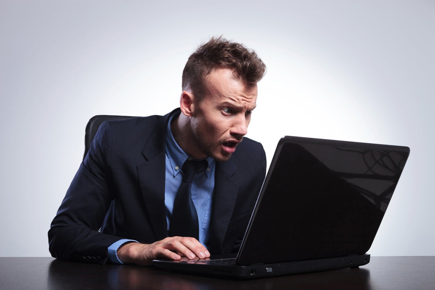 Man sitting at his laptop and looking surprised while reading something.
