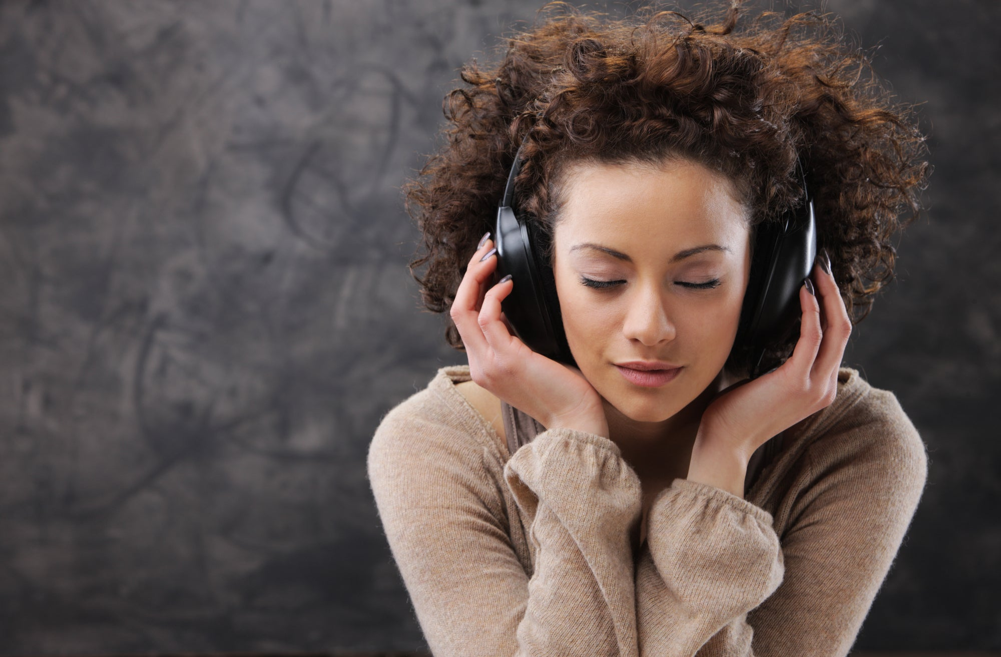 a woman with her eyes closed listening to something with headphones