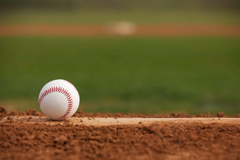 A baseball sits on a pitcher's mound.