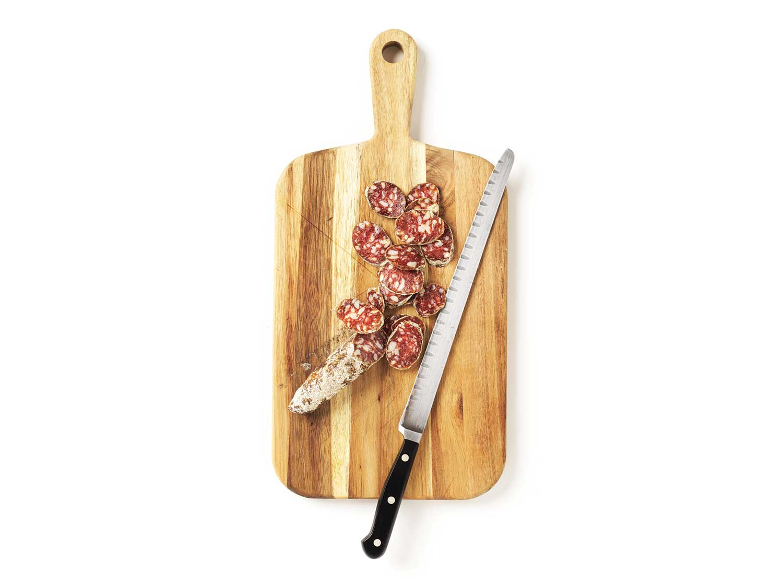 Salami cut on cutting board with knife.