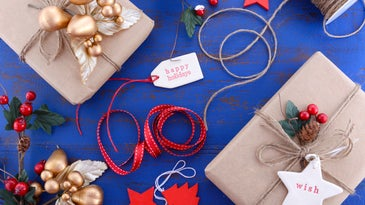 Gift wrapping presents in natural rustic theme brown kraft paper with string and ornaments on a dark blue rustic wooden table.