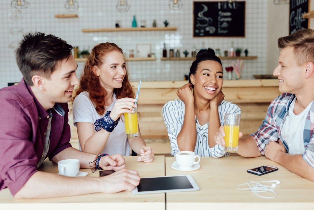 a group of friends drinking orange juice and coffee or tea at a shop while talking about things, maybe podcasts