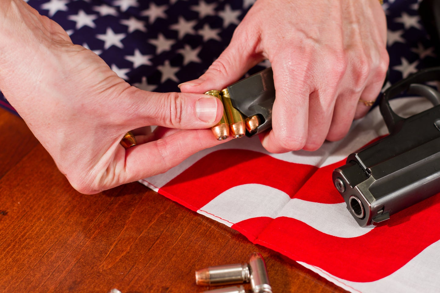 hands load a gun in front of an american flag
