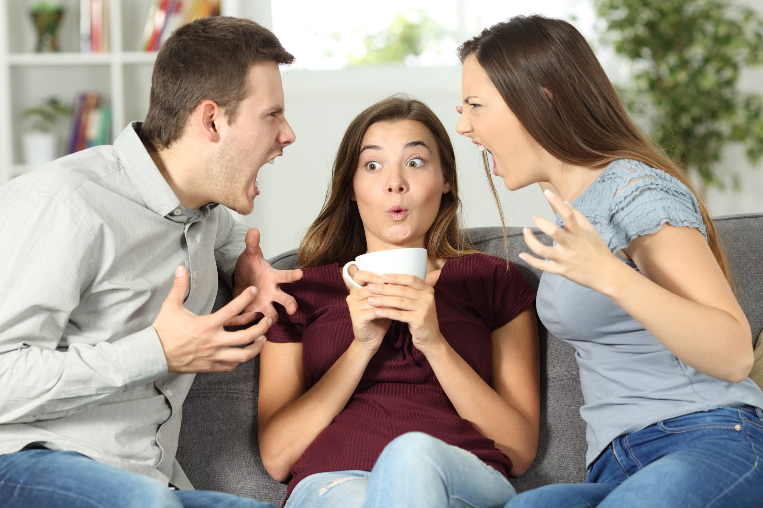 two people arguing with one person sitting awkwardly between them