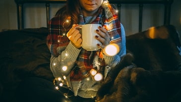 woman holding a cup wrapped in lights and a blanket