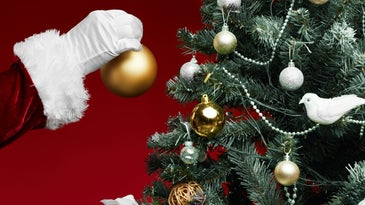 A hand in a santa suit reaches to put an ornament on a decorated christmas tree