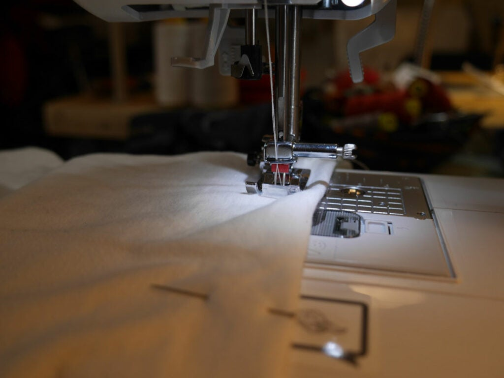 a sewing machine stitching a t-shirt hem with a double needle