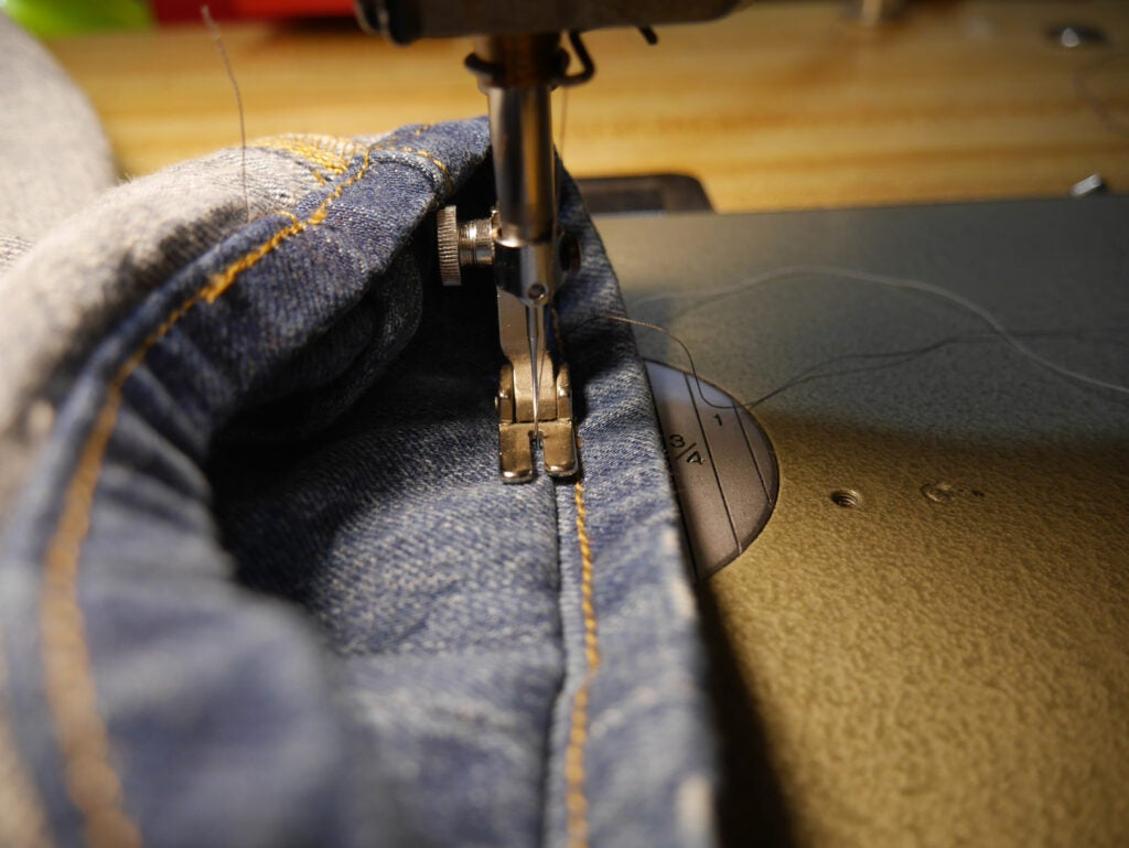 a sewing machine stitching jeans in the Hollywood Hem style