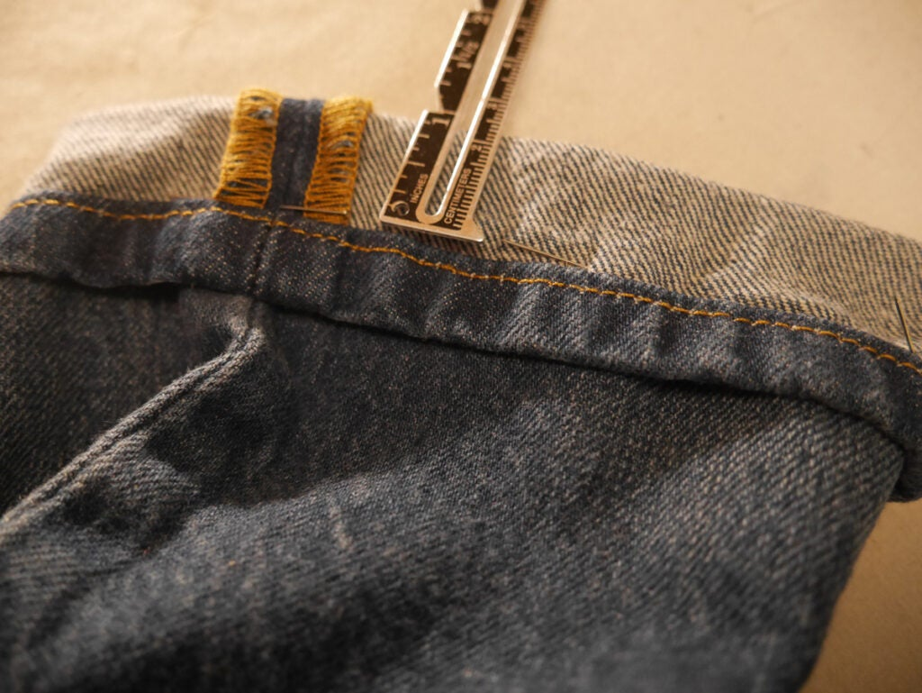 a photo of jeans being hemmed in the Hollywood Hem style, with a ruler