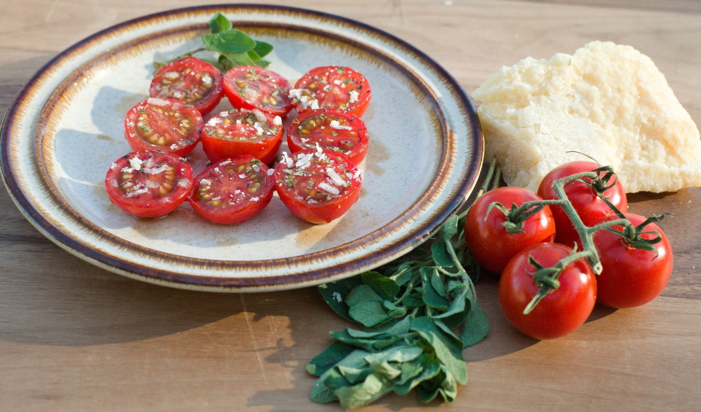 halved cherry tomatoes on a plate with marjoram, parmesan cheese, and other spices