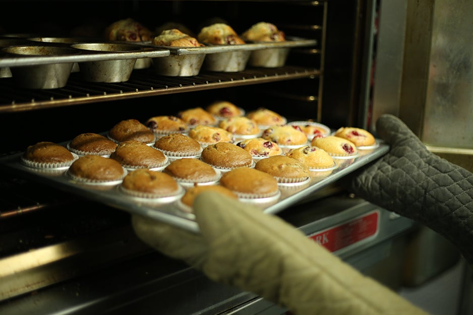 person pulling muffins out of an oven