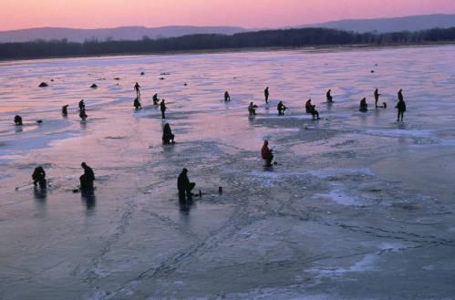 People Ice fishing on frozen lake.