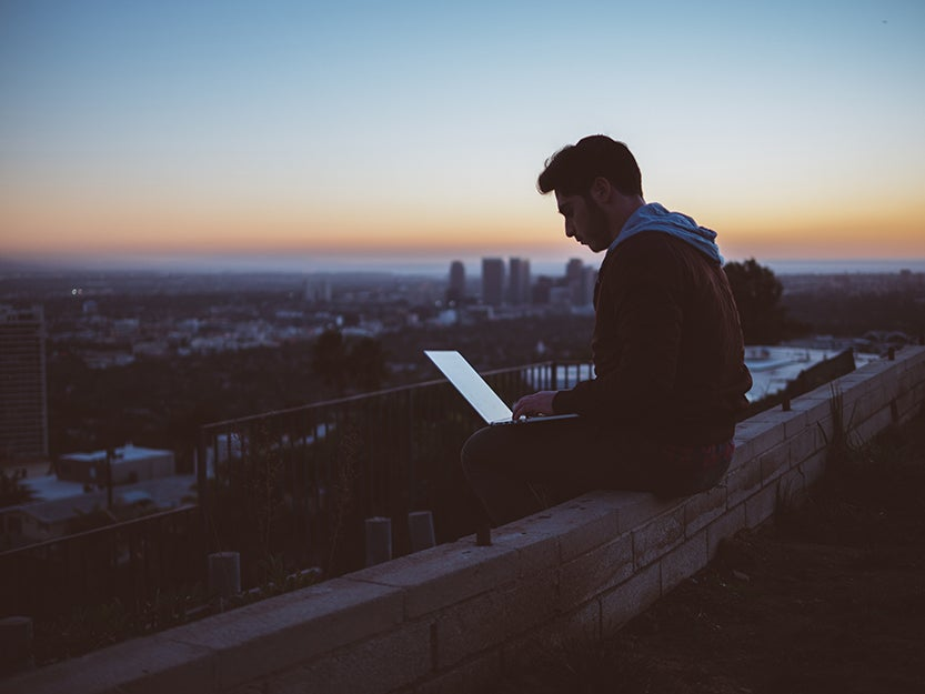 person sitting on a ledge with computer