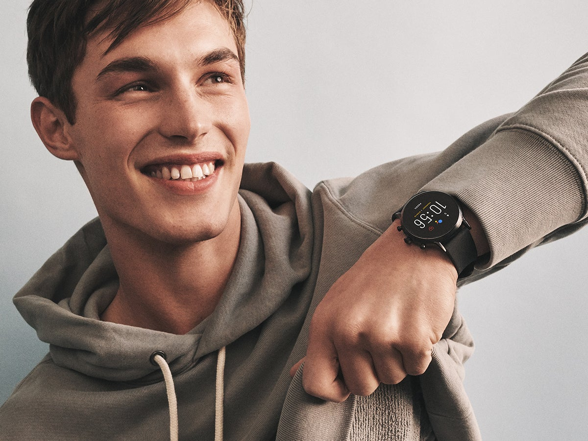 a young man wearing a Fossil smartwatch and lifting up his sweatshirt