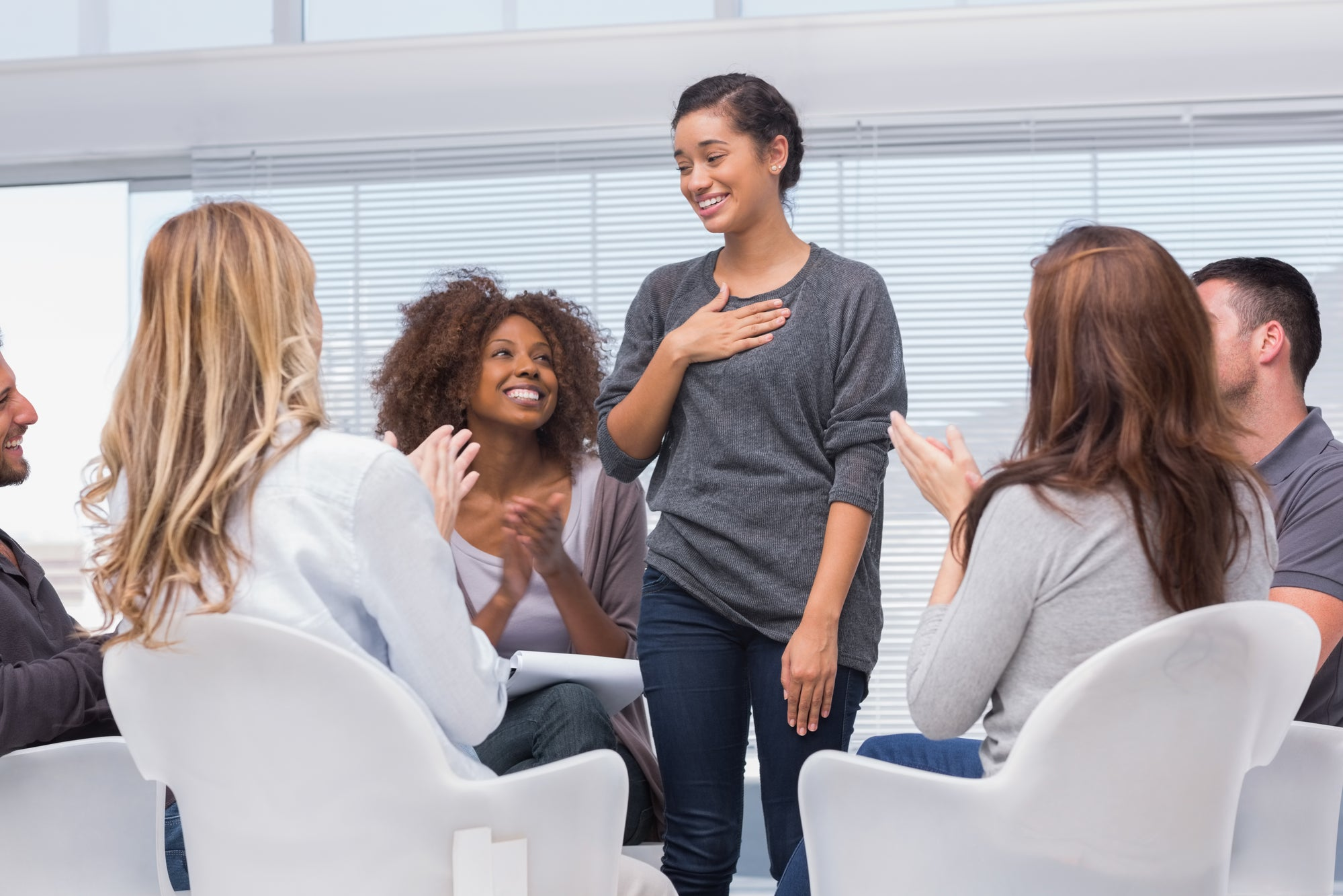 a woman standing up and smiling in group therapy