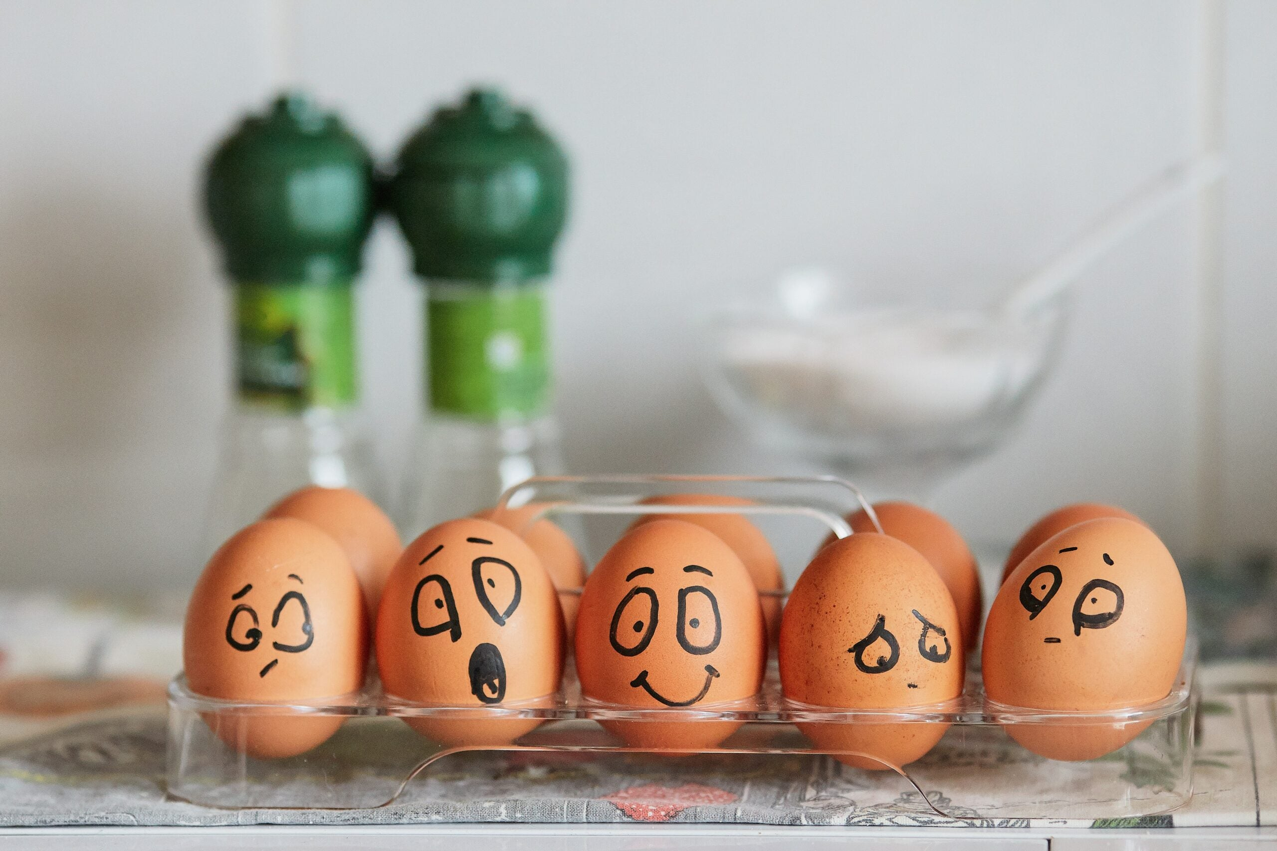A carton of brown eggs with faces drawn on