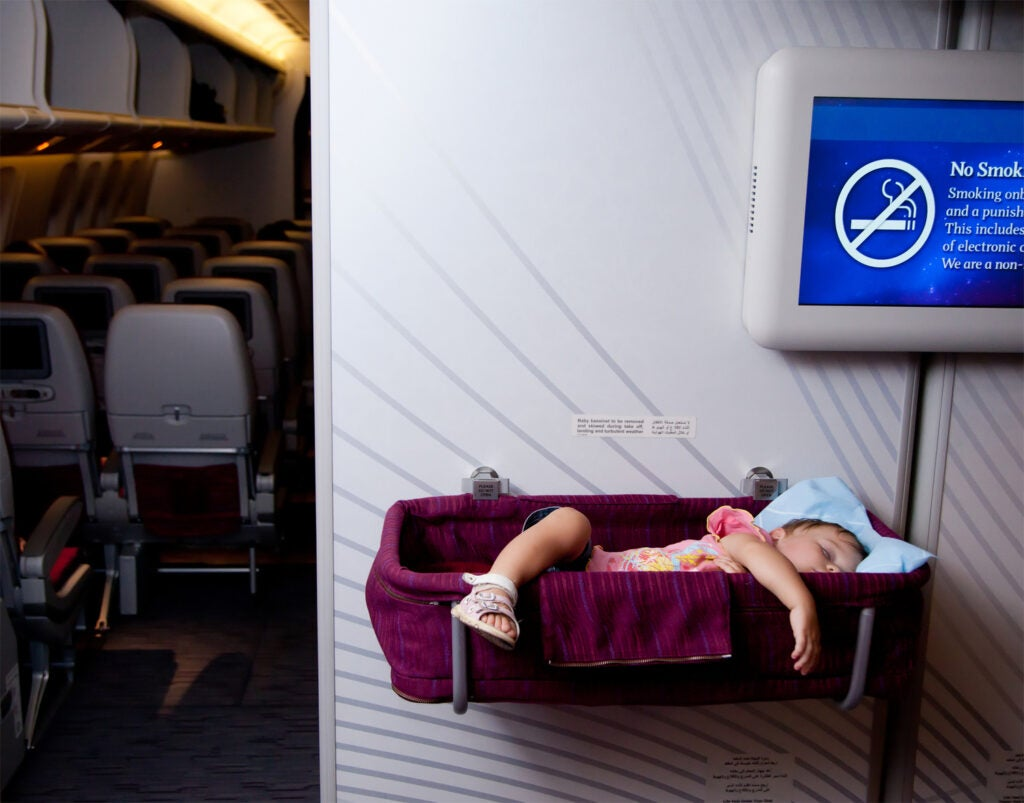 Small two year old baby girl sleep in a special bassinet on a airplane