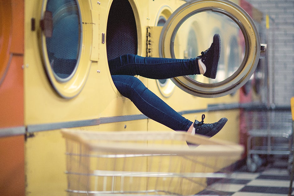 person with legs sticking out of washing machine