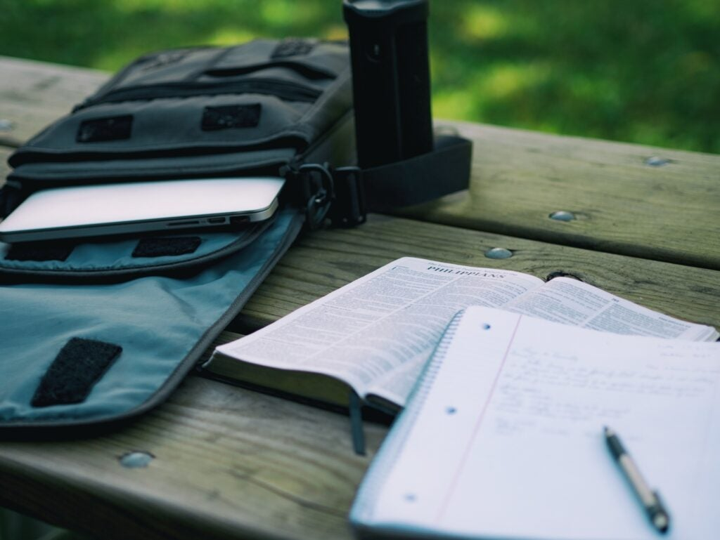a backpack with a laptop in it on a wooden table outside, with an open book and a notebook and pen