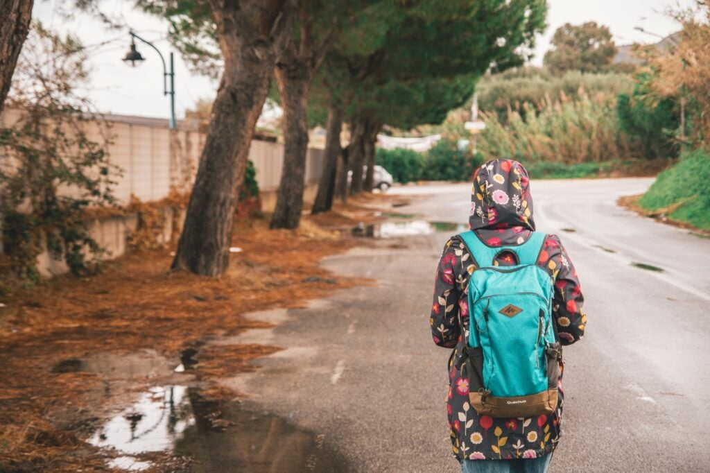 a person in a rain jacket walking on a wet road while wearing a teal backpack