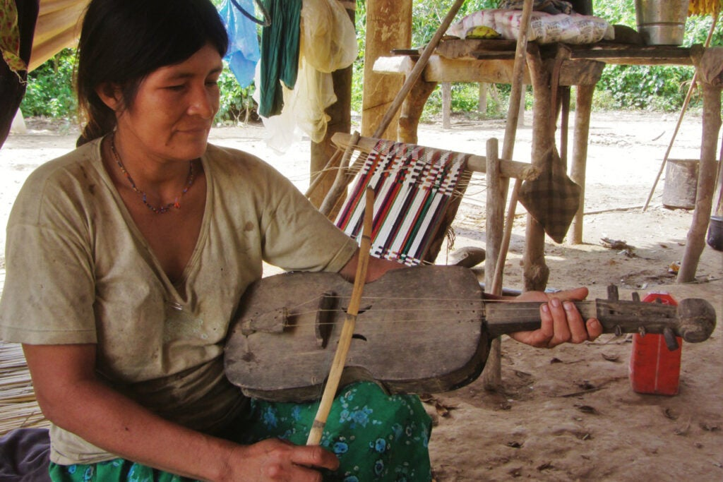A Tsimane' woman in Bolivian Amazonia playing a handmade wooden violin