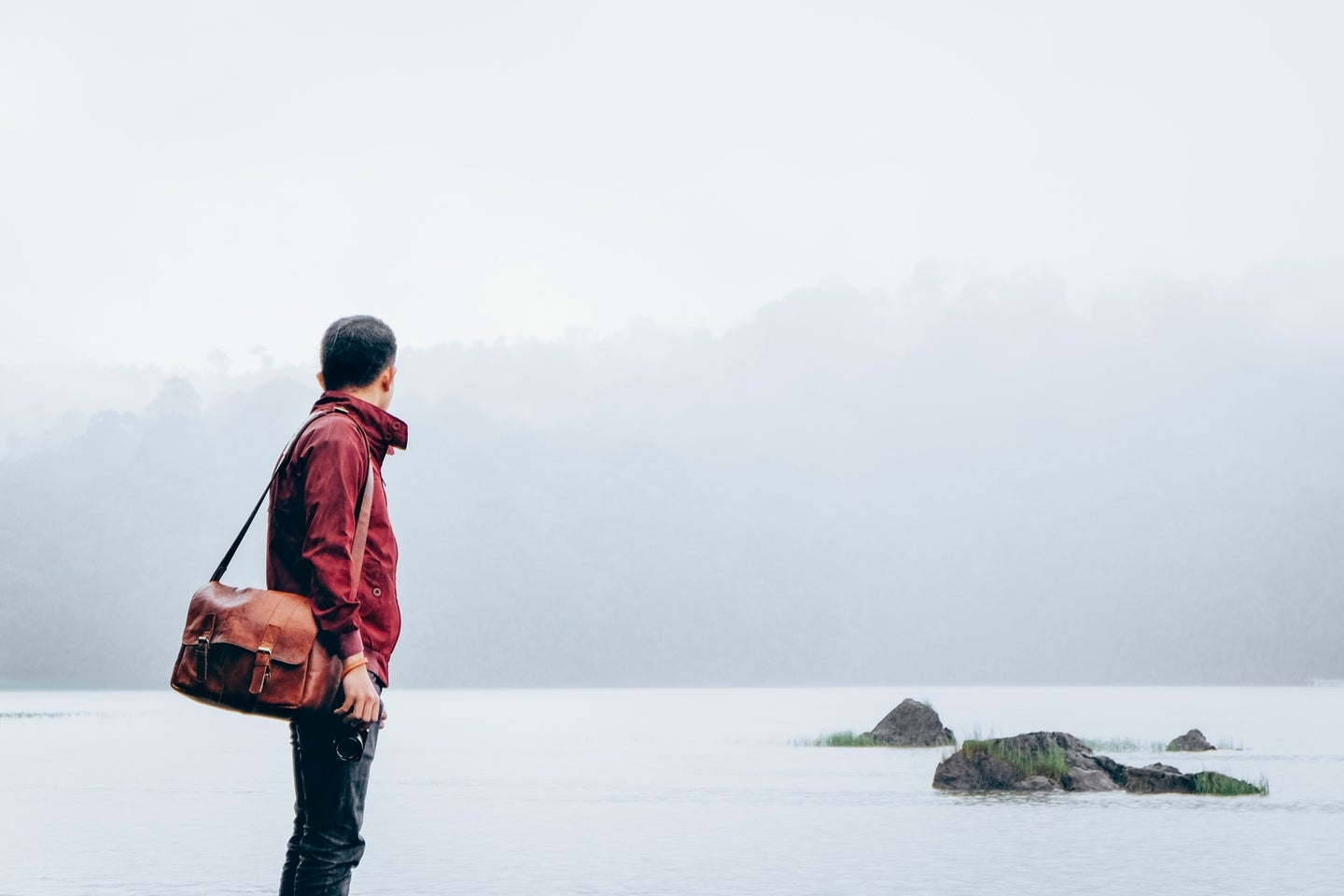 a man in a red jacket and jeans carrying a brown leather messenger bag and staring out at gray water and some rocks covered in fog on a cloudy day
