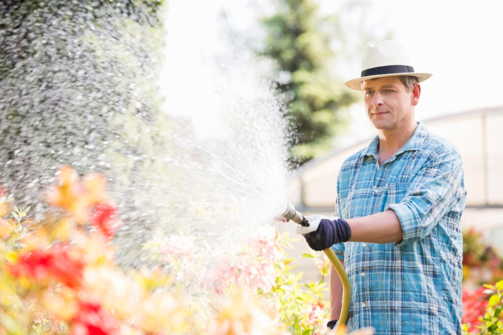 Person watering plants outside greenhouse