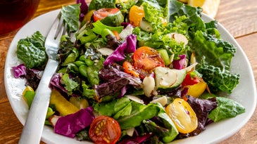 Close up of fresh organic super food salad in white bowl with fork on side and olive oil, red wine vinegar and lemons