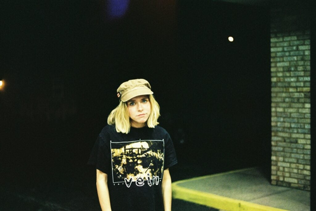 a blonde woman in a black t-shirt standing outside a building in a parking lot at night