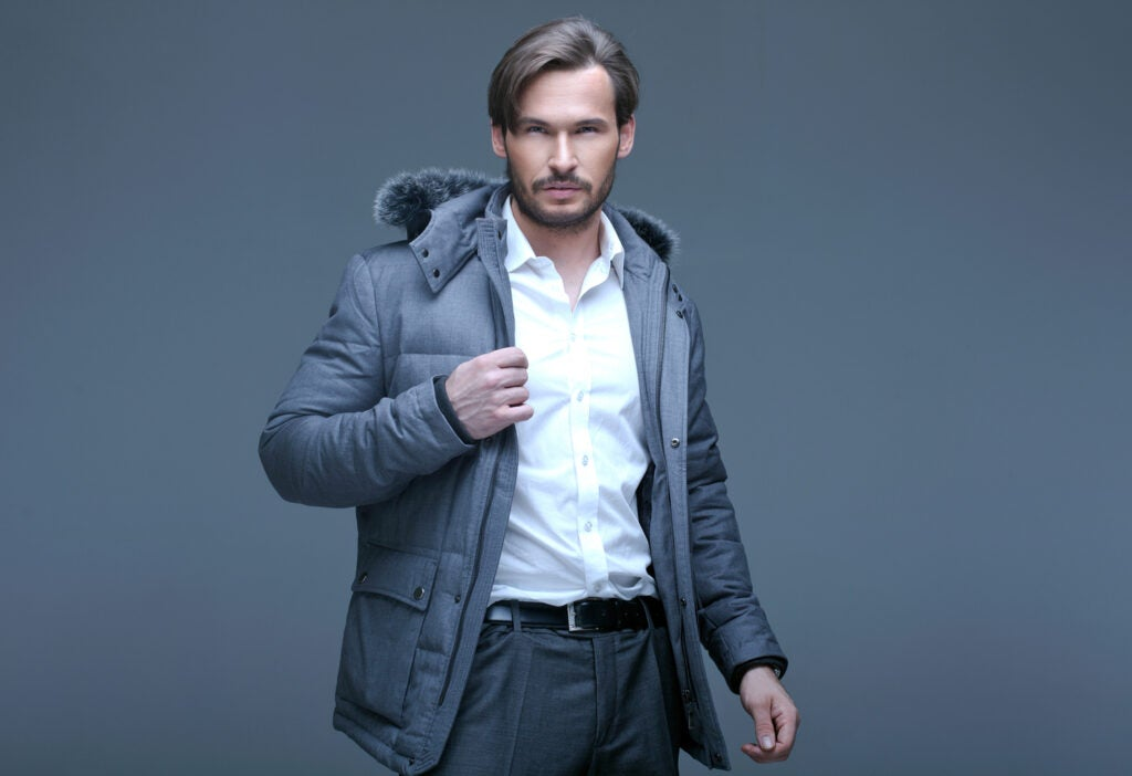 a handsome man in a puffy winter jacket with a patch pocket, dress shirt, and pants