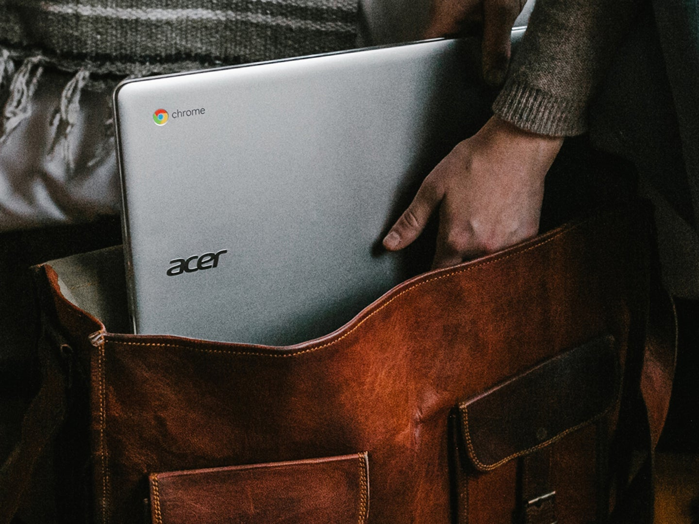 Hand in leather bag with Chromebook laptop