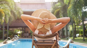 a woman in a sun hat sitting in a chair by a pool at a tropical resort hotel