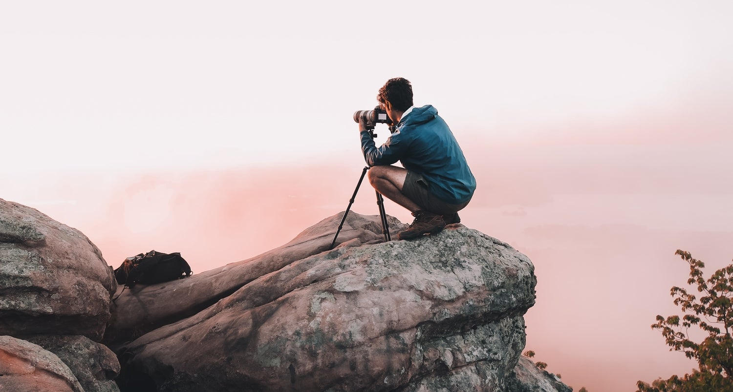 Person taking photo on high rock
