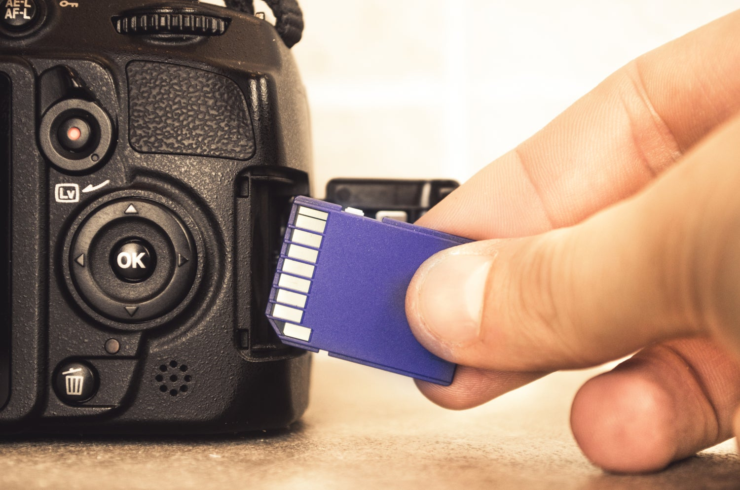 Hand inserting SD card into DSLR camera