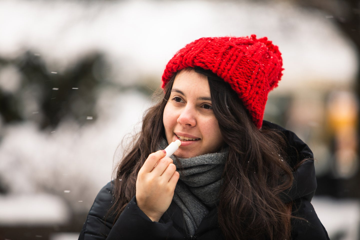 woman using cream at cold winter weather. skin protection. dry face
