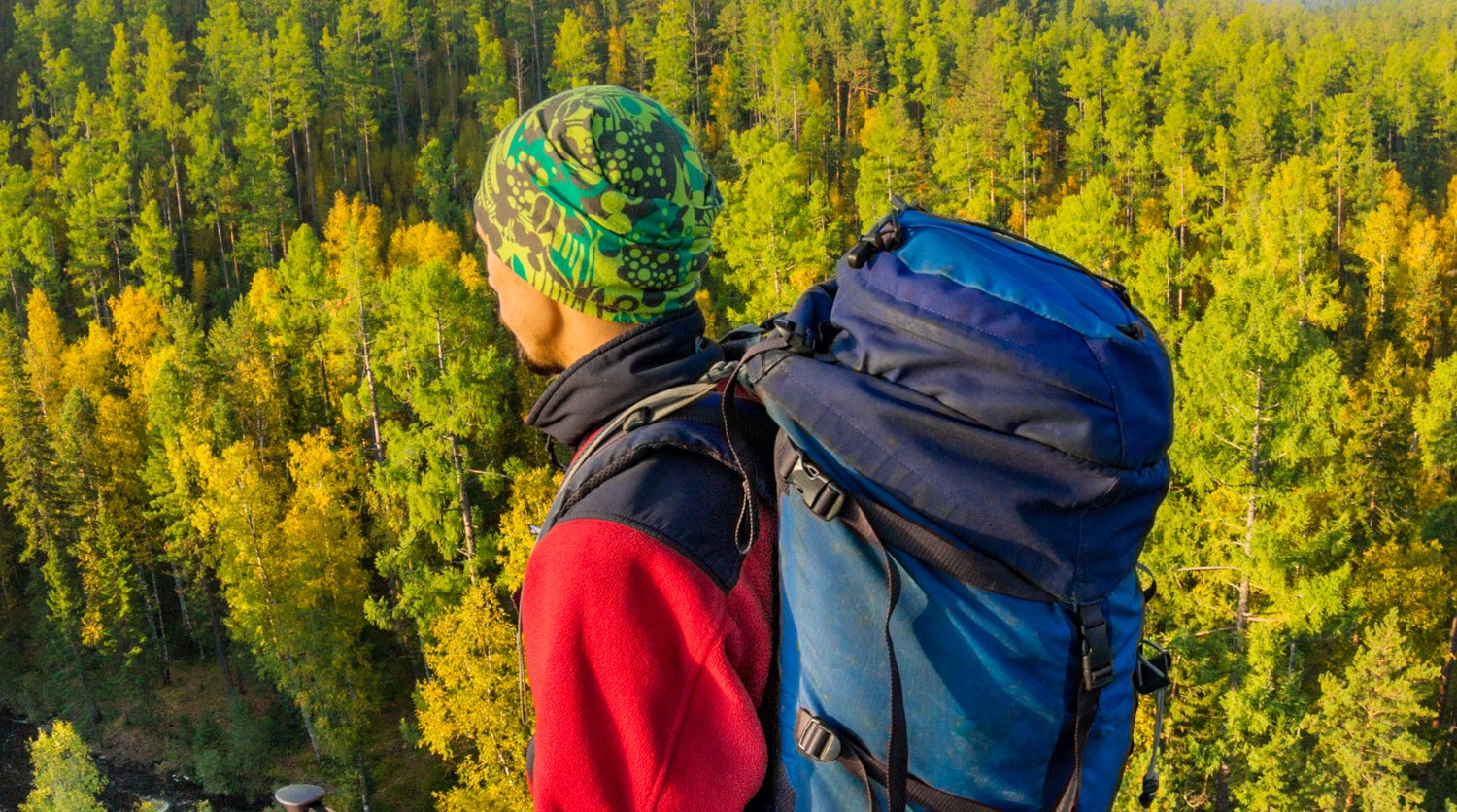 Man with backpack and trekking pole in bandana standing on a rock at dawn above a background autumn forest.