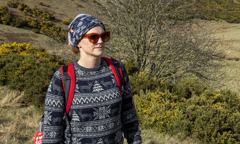 A person hiking while wearing a neck gaiter or a bandana around their head.