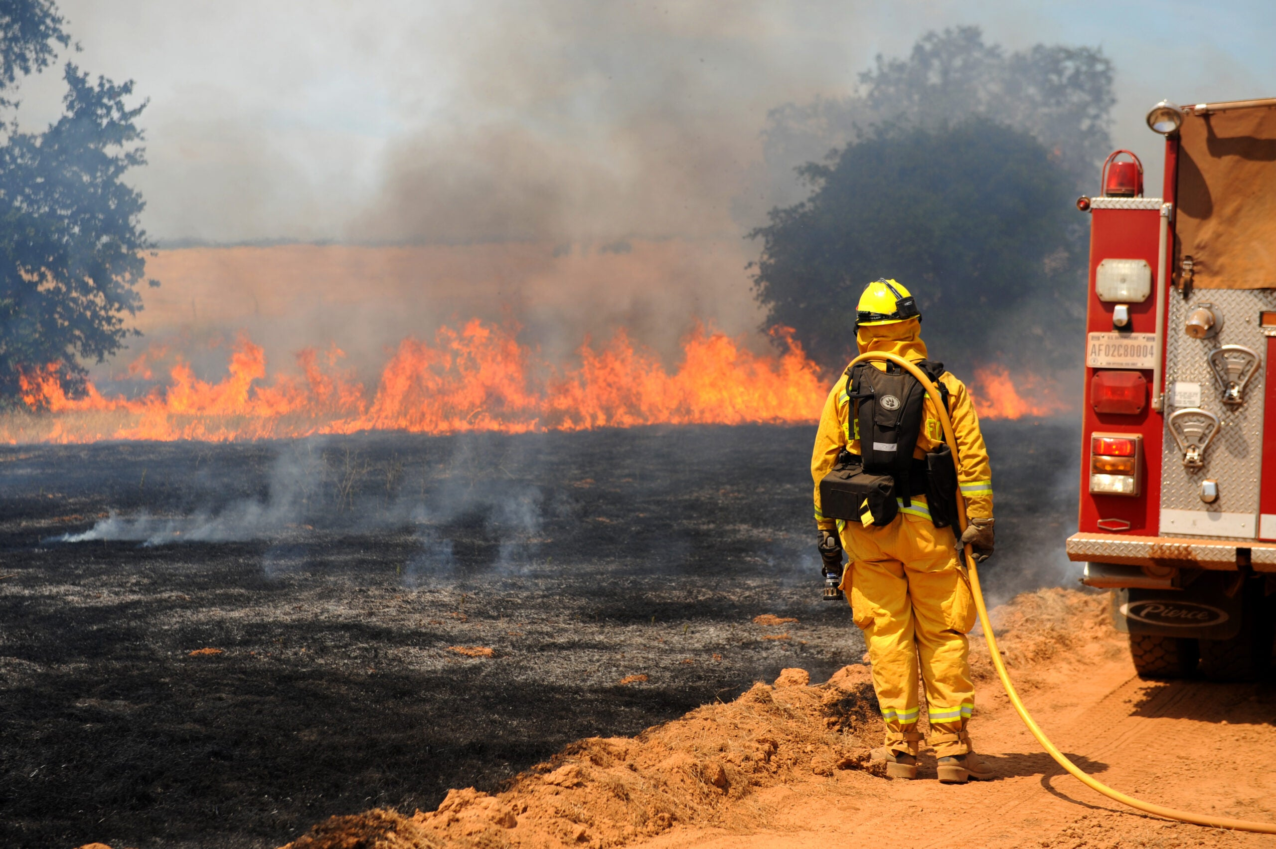 firefighter looks out over burned land and fire