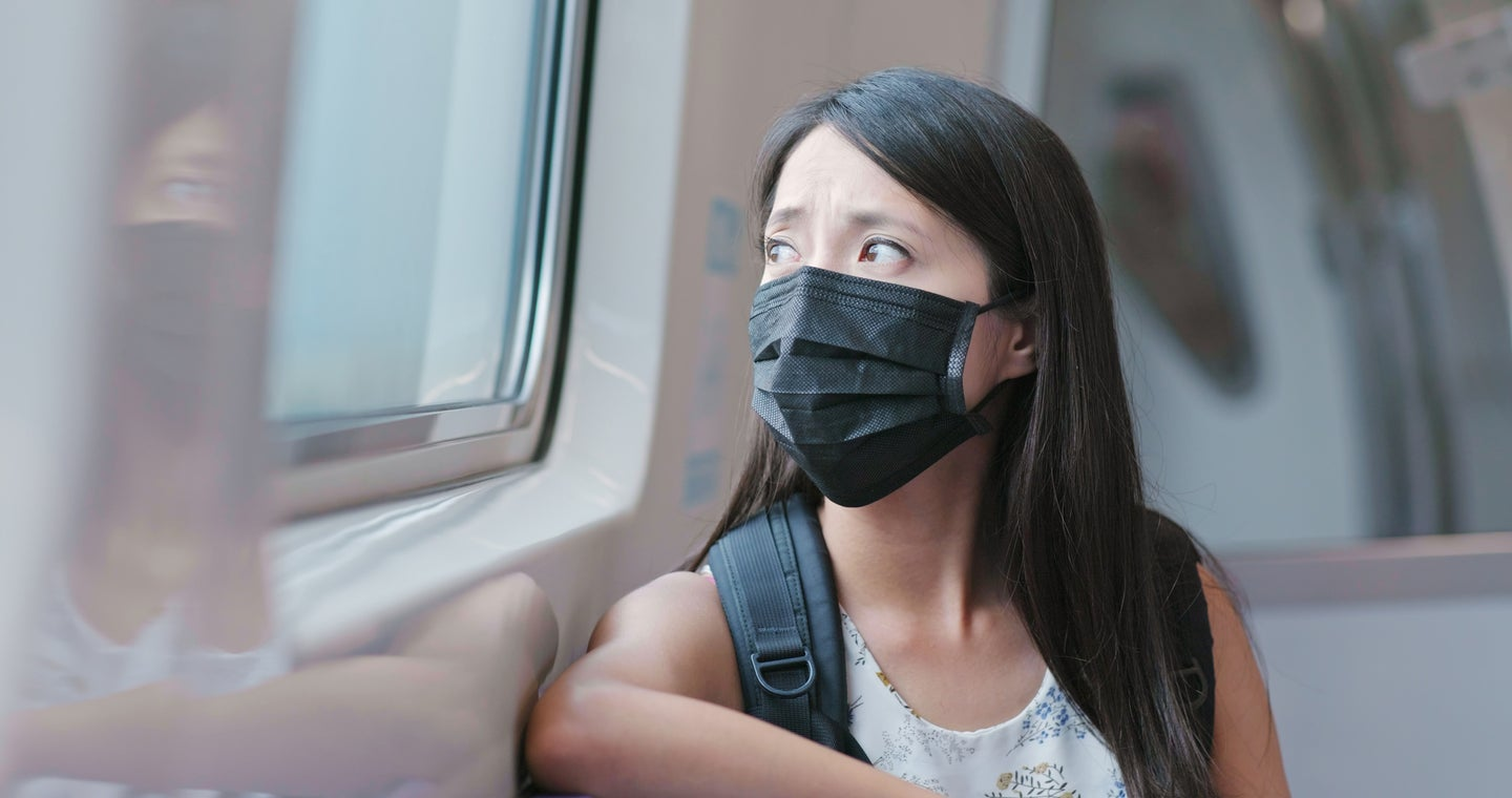 a woman wears a black face mask on the train in Taipei city in taiwan