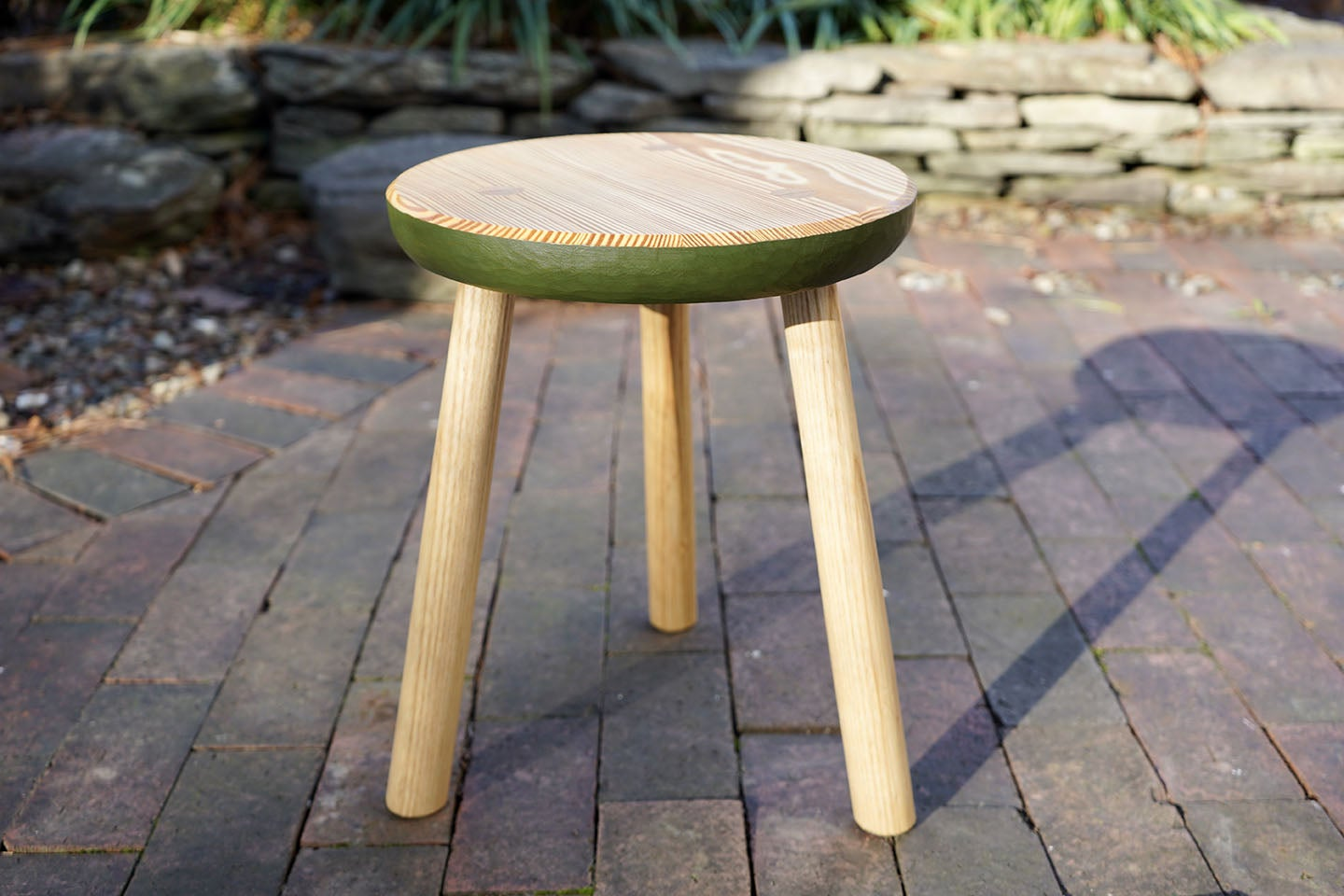 a wooden three-legged stool on a brick patio