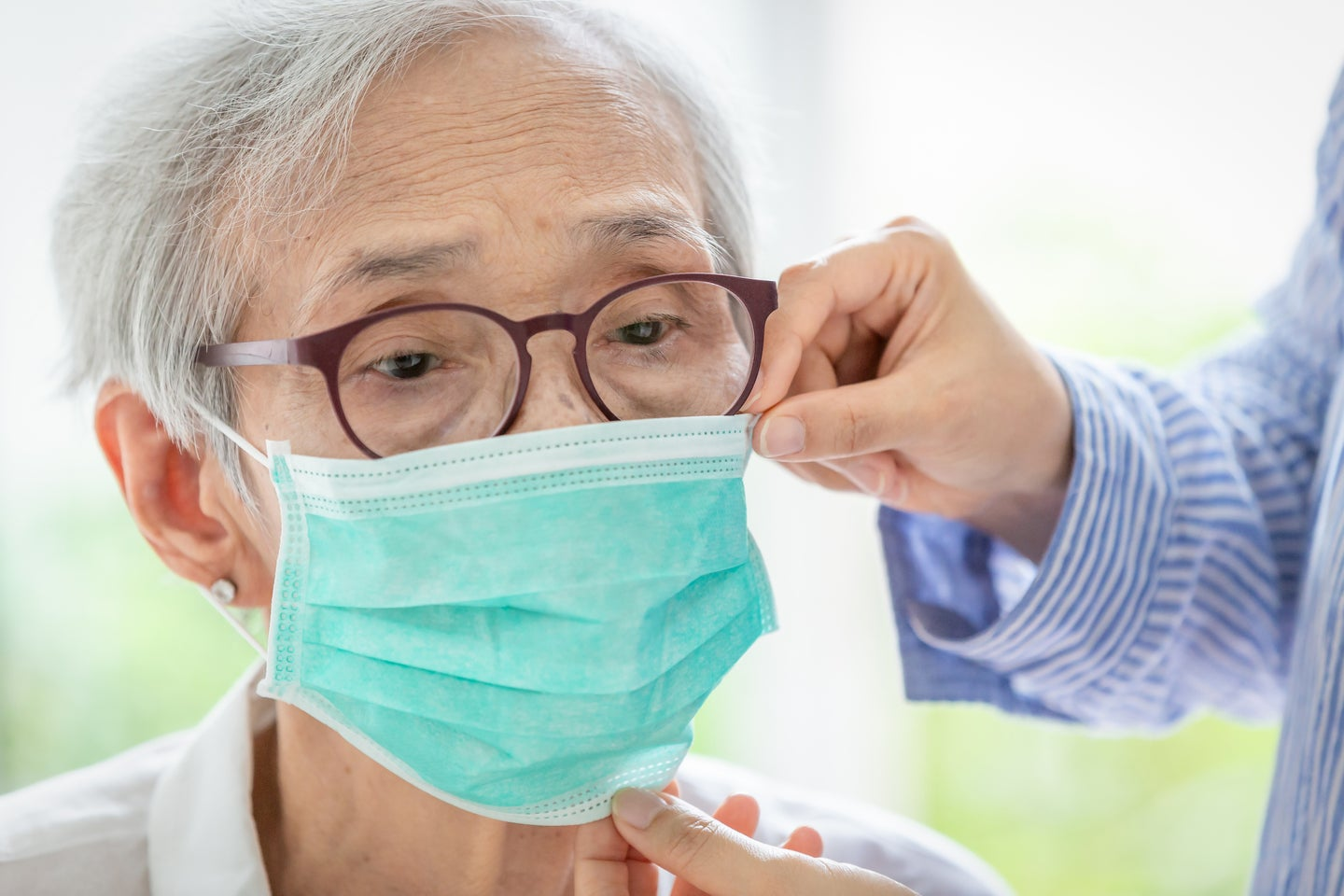 someone helps an older woman put on a face mask