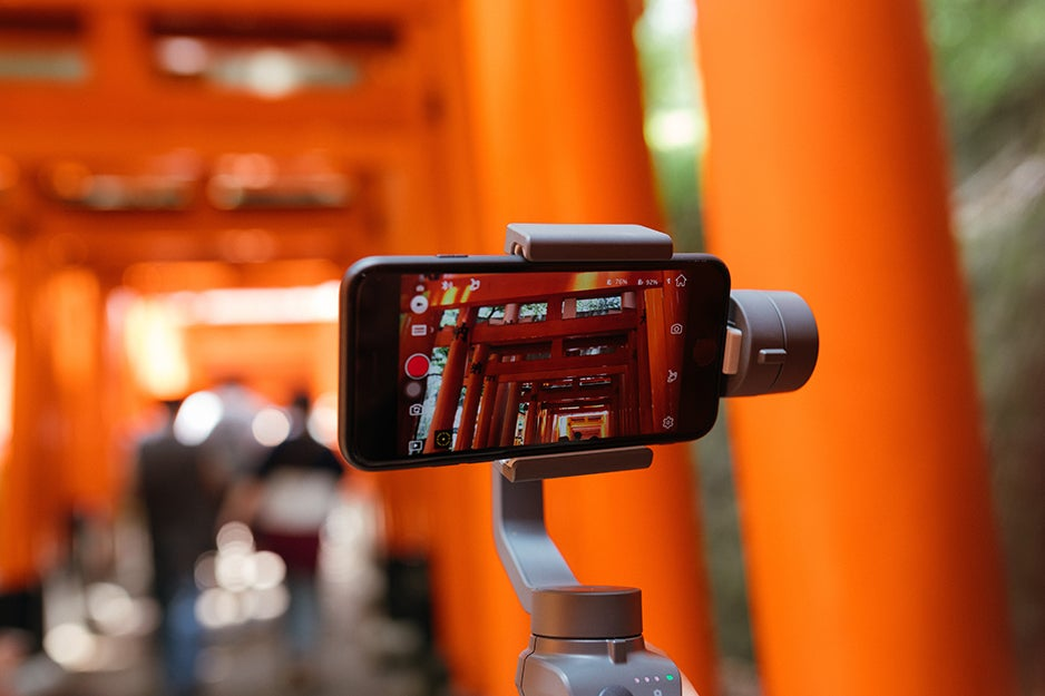 person holding a gimbal and smartphone