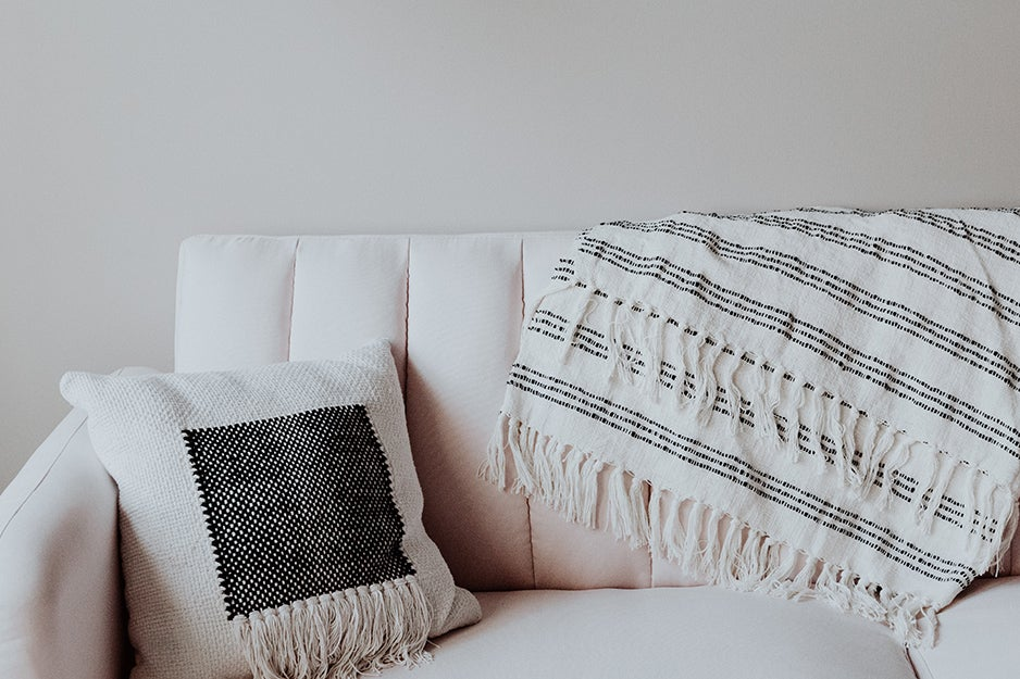 couch with pillow and throw blanket
